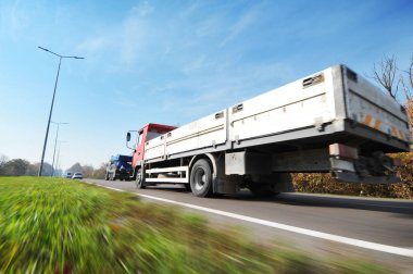 Flatbed truck and cars in motion on countryside road against sky