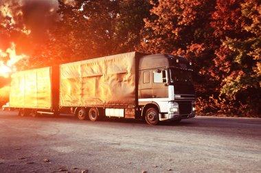 Truck on highway in autmun on yellow sunset