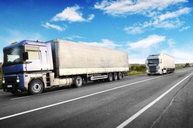 Big trucks and white trailers with space for text on countryside road against blue sky with clouds