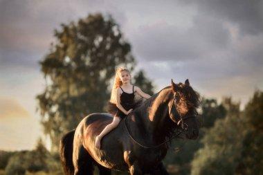 Little ballerina girl with black friesian stallion