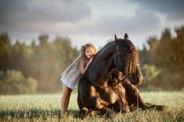 Little  girl with black friesian stallion