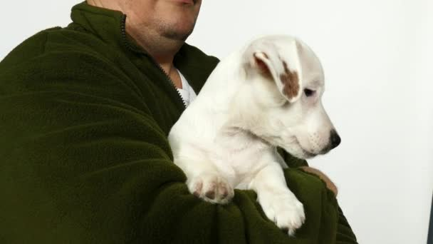 Man in in an green sweater holds a puppy in his arms.