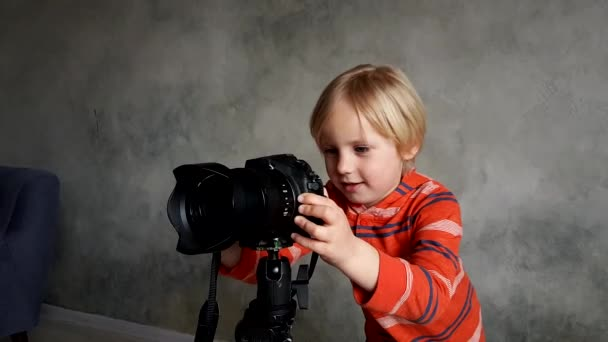 ein Junge spielt mit einer echten Fotokamera