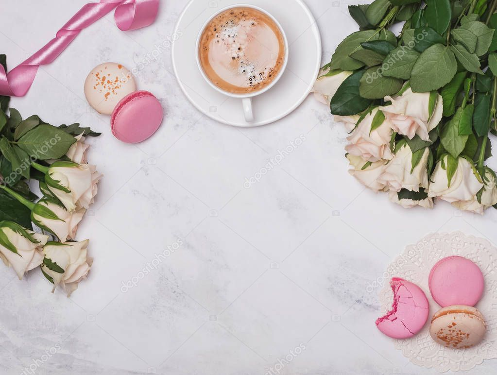 White roses, coffee and macarons on the marble background