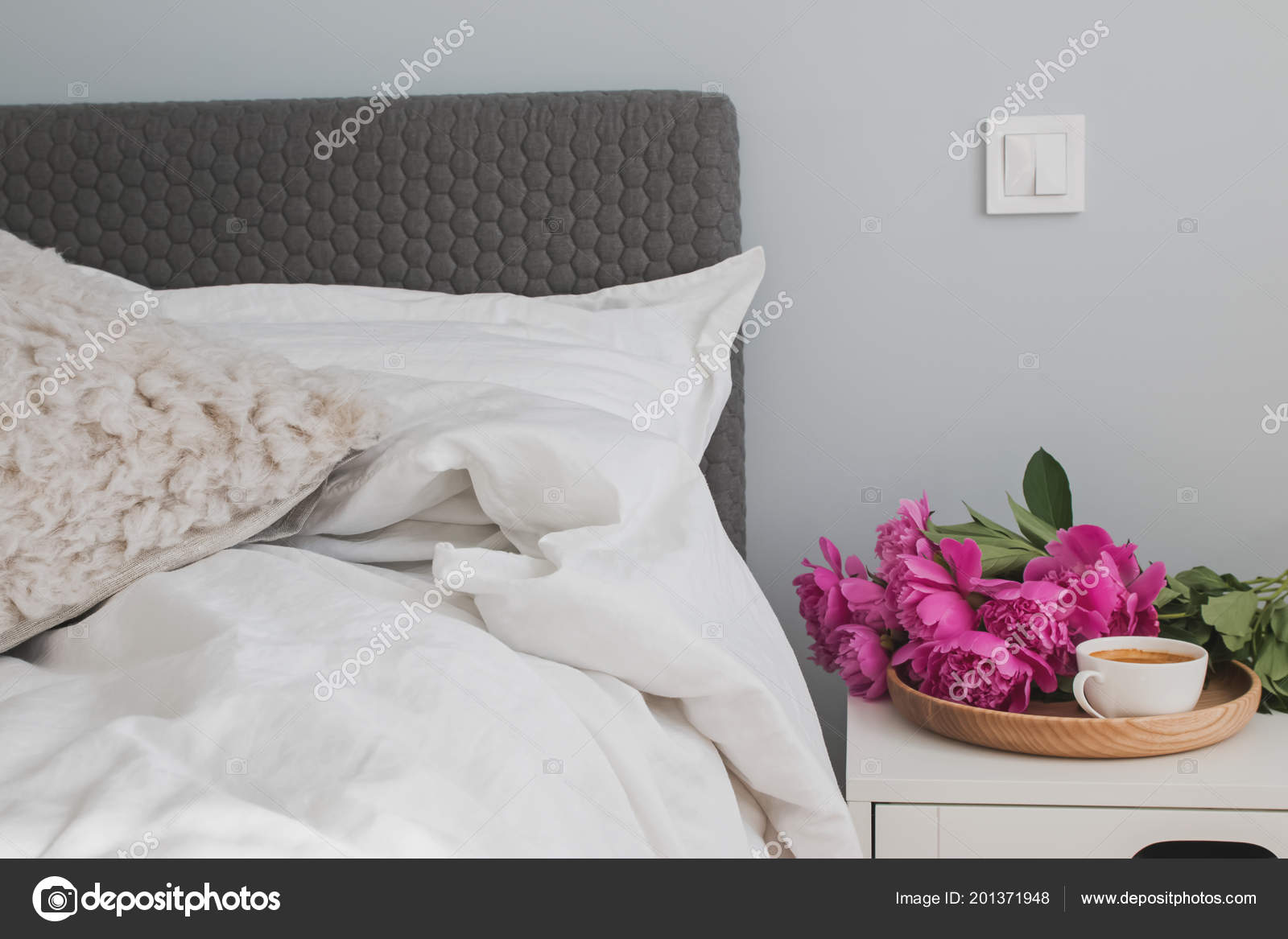 Bed with white bed sheets and pink peonies and coffee on the ...