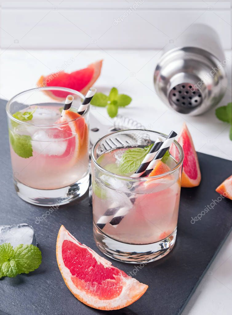 Two glasses of grapefruit cocktail with mint close-up