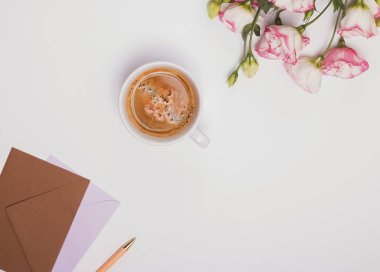 Coffee, flowers and envelopes on the white.