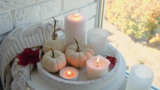 Svíčka hoří na stole s podzimní výzdobou