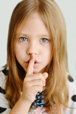 girl placing finger on lips asking shh, quiet, silence