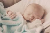 roztomilý novorozené miminko spí v postýlce