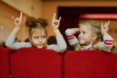 two funny girls sitting on the seats and waiting childrens show