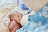 Fotografie Mutter stillt Baby in ihren Armen zu Hause