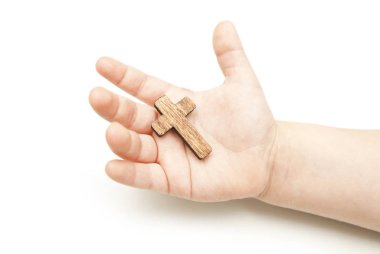 A little wooden cross in the child's hands