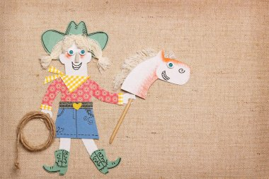 Cowgirl in western clothes with cowboy lasso and stick horse toy in hands.Paper cut application background for text