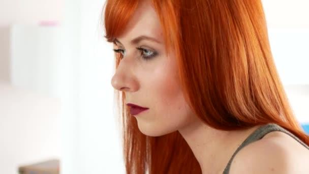 Zrzavý žena vyrovnávání vlasy žehličkou před zrcadlem