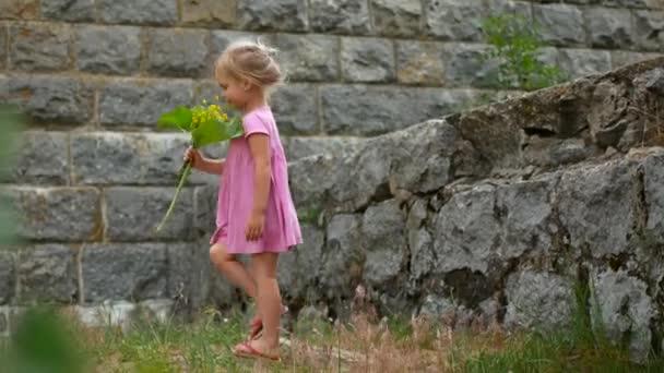 Dívka v růžových šatech s kytice divokých květů