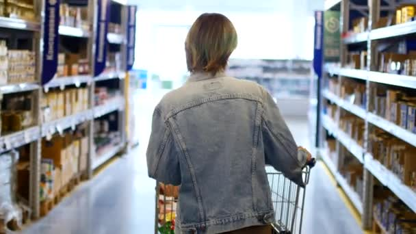 Woman shopping at the supermarket, follow shot from back of young woman with trolley in shopping center