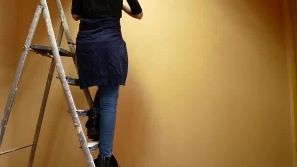 Künstlerin malt eine Wand, die auf einer Leiter steht
