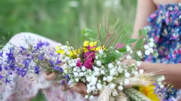 Female hands make a wreath of summer wildflowers