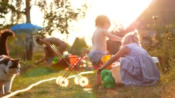 Glücklich fröhliche Kinder im Sommerurlaub mit Wasser spielen. Süß lächelnd entzückende Kinder Sprühen mit einem Gartenschlauch in den Hinterhof. Nahaufnahme
