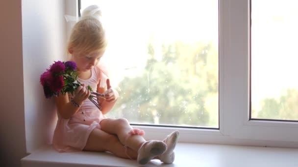 die junge Ballerina sitzt am Fenster und hält Blumen in ihren Händen