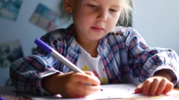 Roztomilá malá dívka sedí u svého stolu a kreslí pastelkami.