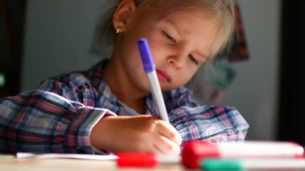 Aranyos kis lány ül az asztalnál, és felhívja a ceruzák.