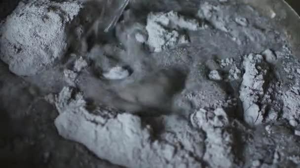Arbeiter, die Zugabe von Wasser in den Behälter mit grauen Sichtbeton