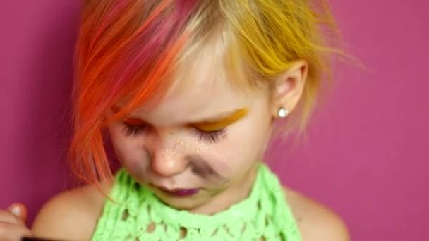 Malá blondýnka dělá make-up. Jasný módní video