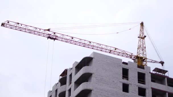 Stavba multistory, cihlové budovy. Montážní jeřáb zdvihá stavební materiály.