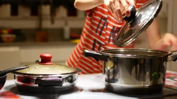 Házi feladat a konyhában, egy forró fazékba a hostess eltávolítja a fedelet