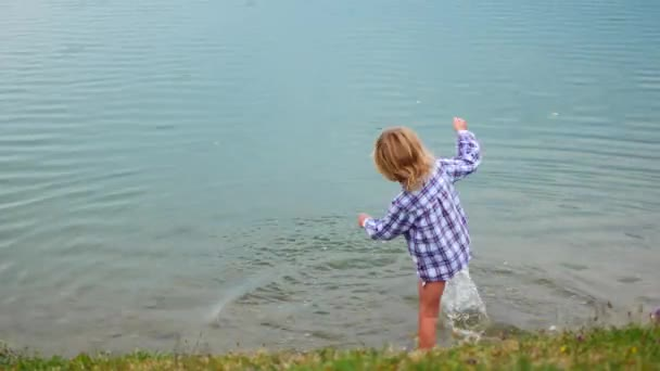 Kind sprüht seinen Fuß auf den See