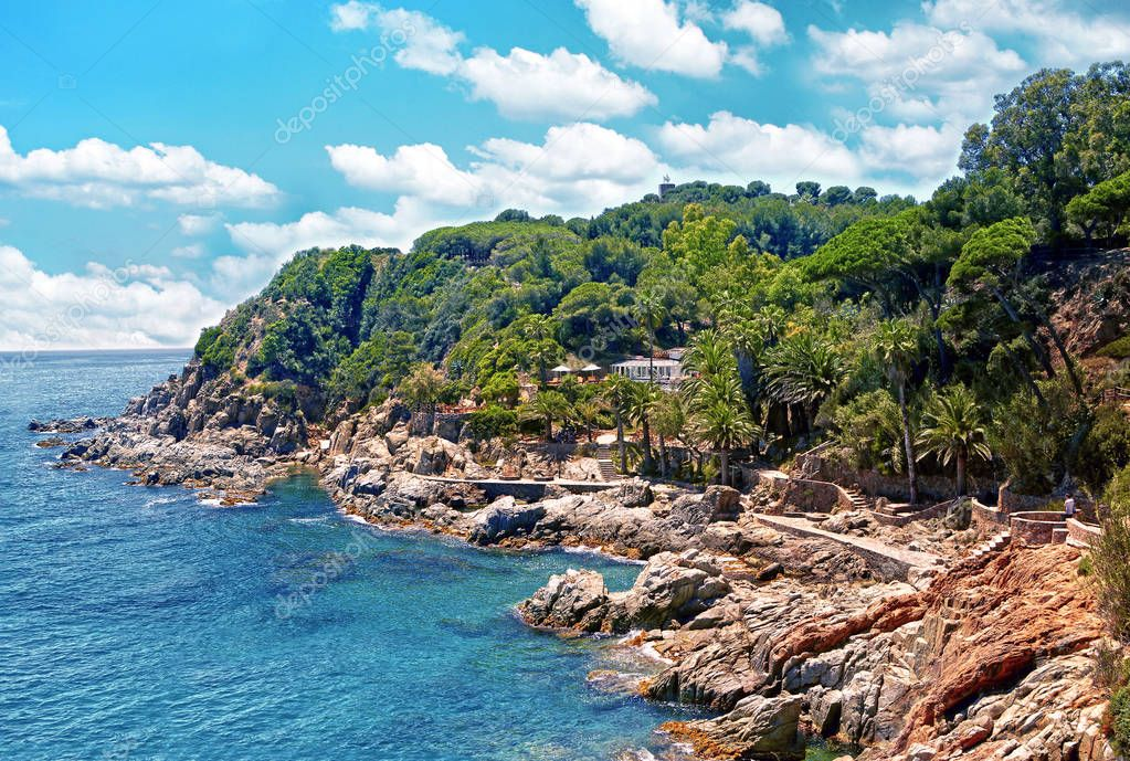 Beautiful scenery wild coast and beach bay of Spain, turquoise sea water, picturesque rocks against the blue sky with clouds