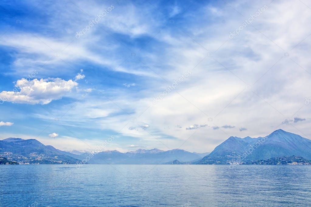 Beautiful landscape of the Alpine mountains on the Lago Maggiore lake against the background of a cloudy blue sky, Italy