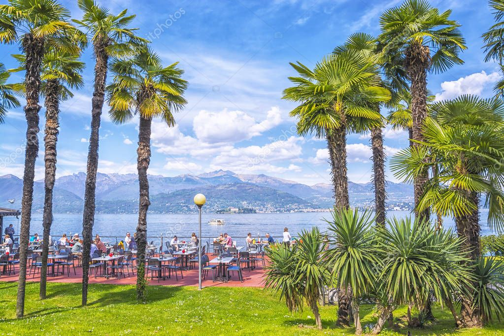 Stresa, Italy - April 11, 2017: Outdoor restaurant with beautiful view on Lake Lago Maggiore in the background of the Alps Mountains in resort town of Stresa, Italy.