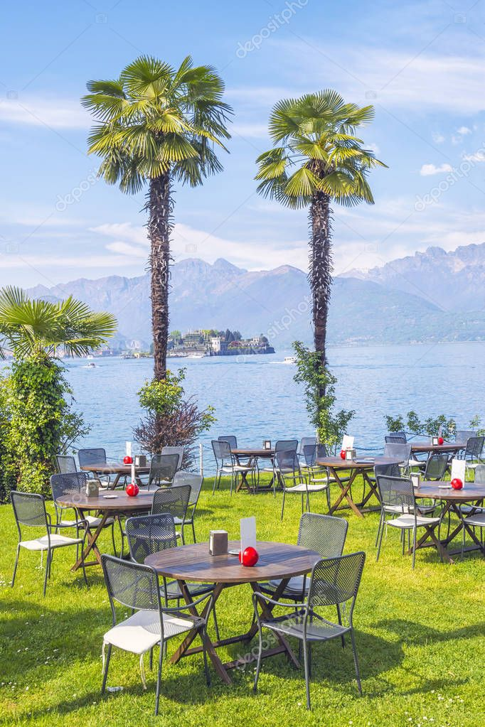 Outdoor restaurant with beautiful view on Lake Lago Maggiore in the background of the Alps Mountains, Stresa, Italy