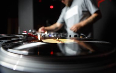 Professional dj turntable records player in close up. Disc jockey mixing music on background. Sound recording studio equipment