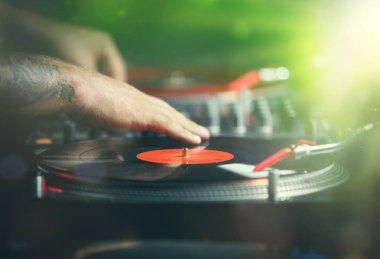 Hands of professional club dj scratching vinyl disc on turn table player device.Retro djs audio equipment in use on concert stage.Party disc jockey plays live set with analog records with music