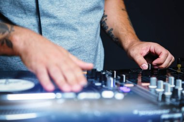 Professional disc jockey scratches vinyl records with hip hop music on night club party event.High quality audio equpment for pro disc jockey.Focus on hands of musician mixing musical tracks in stage