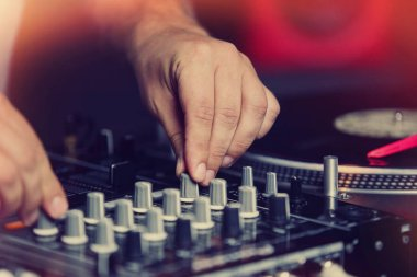 Club dj playing music on party.Nightclub disc jockey adjust sound frequency on professional sound mixer panel.Focus on djs hands holding regulator