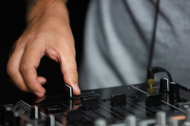 Hand of disc jockey adjusting the crossfader knob while palying live set on party in night club