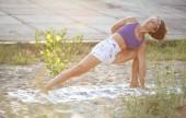 Jóga dívka táhnoucí venkovní při západu slunce. Sportovní mladá běloška sportovní cvičení na fitness program pro pevné zdraví. Zdravý životní styl a wellness koncept