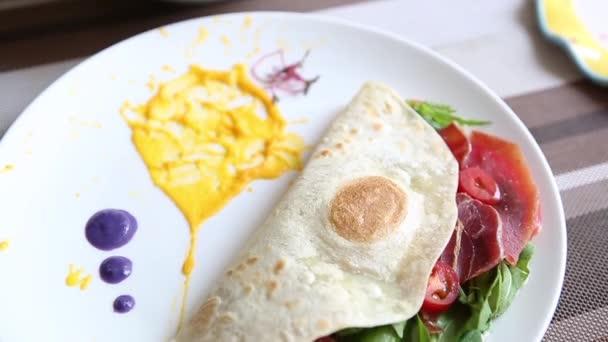 köstliche Tortilla mit Marmeladenschinken-Scheibe serviert mit Spinat und Tomaten zum Mittagessen im Café. leckere gesunde Jause für Brunch-Menü im Restaurant. Gutes Essen mit natürlichen Zutaten genießen.
