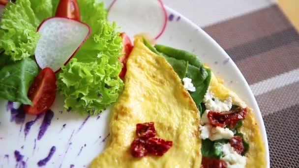 Lahodná omeleta misky se sušenými rajčaty, řecký feta sýr, čerstvý zelený špenát listy servírované na bílé plotně v kavárně brunch. Chutná přírodní jídlo k obědu v restauraci. Užijte si jídlo omlet ráno.