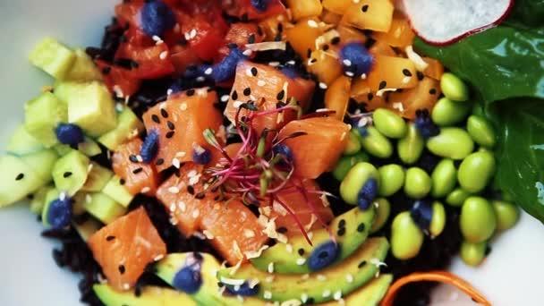 Leckeren frischen Salat. Lachs Fisch, grüne Bohnen, Avocado, schwarzer Reis, serviert in weiße Schüssel Schale am Tisch im Café geschnitten. Aufnahmen von Naturkost für das Mittagessen im Restaurant. Gesunde Ernährung mit reichem Geschmack.