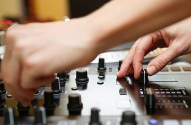 Disc jockey raise volume level on audio mixer.Party dj play music track at concert.Close up,focus on sound mixing controller fader knob.Hands of dj playing music at hip hop party event