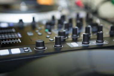 Top class dj audio mixer controller to play music and remix tracks at party in nightclub.Mixing controller knobs and faders in focus.Disc jockey setup for live event in night club