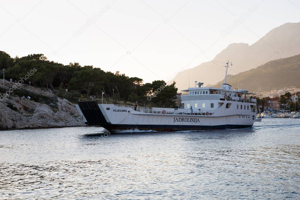 MAKARSKA,CROATIA-29 JUNE,2017: Big ferryboats transports tourists with cars for exotic islands in Adriatic Sea.Ferry ship goes out of haven in Makarska Riviera.Industrial water craft at work