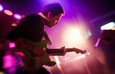 MOSCOW - 13 OCTOBER, 2016 : Russian rap music concert in night club. Hip hop band guitarist performing on stage of nightclub Yotaspace. Electric guitar player playing on scene