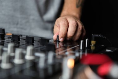 Hand of DJ playing music with professional sound mixer setup on stage in night club. Party disc jockey mixes tracks with crossfader knob